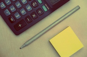 a calculator, pencil, and post-it note pad ready to break down an energy bill
